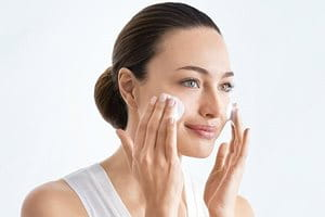 Woman using Cleanser on cheeks